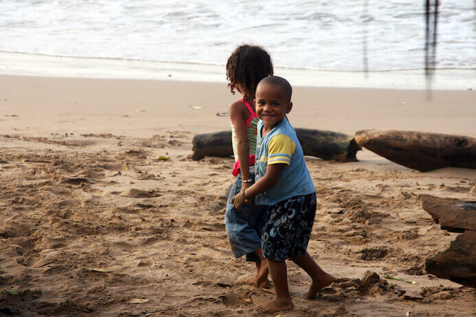 two children holding hands on a beach in Venezuela
