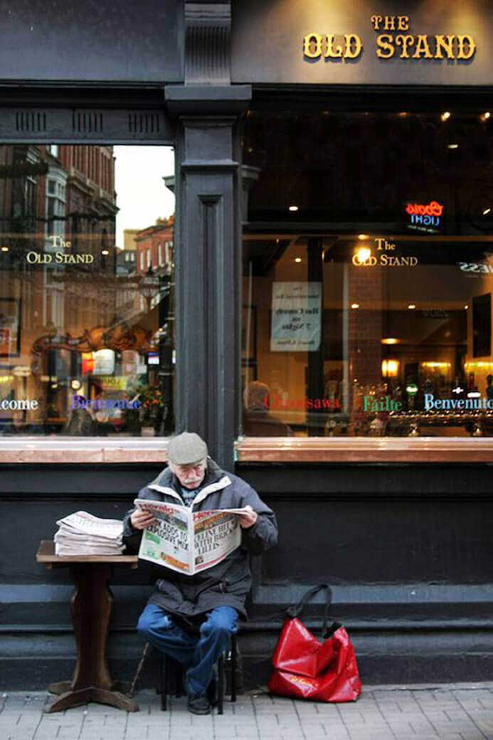 old man reading a newspaper outside a pub in ireland