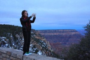 A female taking a photograph of the Grand Canyon