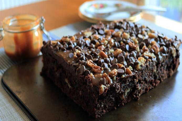 A decedent celebration salted caramel chocolate cake recipe with chocolate frosting and salted caramel sauce topped with nuts and chocolate chips.