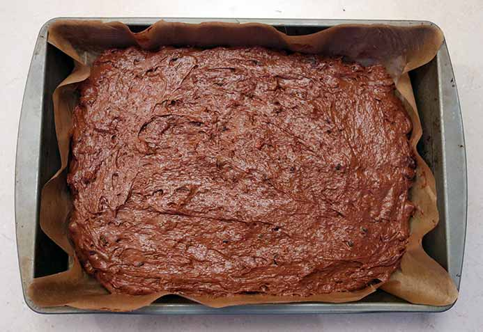 The uncooked cake batter in the sheet pan