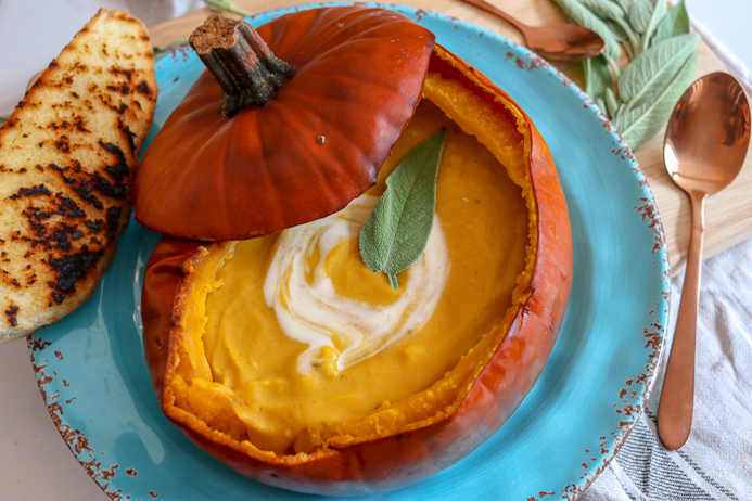 Pumpkin Soup Recipe served in a pumpkin shell garnished with cheese, cream and herbs.
