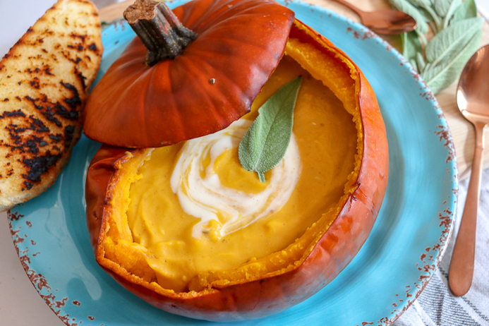 Pumpkin Soup Recipe served in a pumpkin shell garnished with cream and herbs