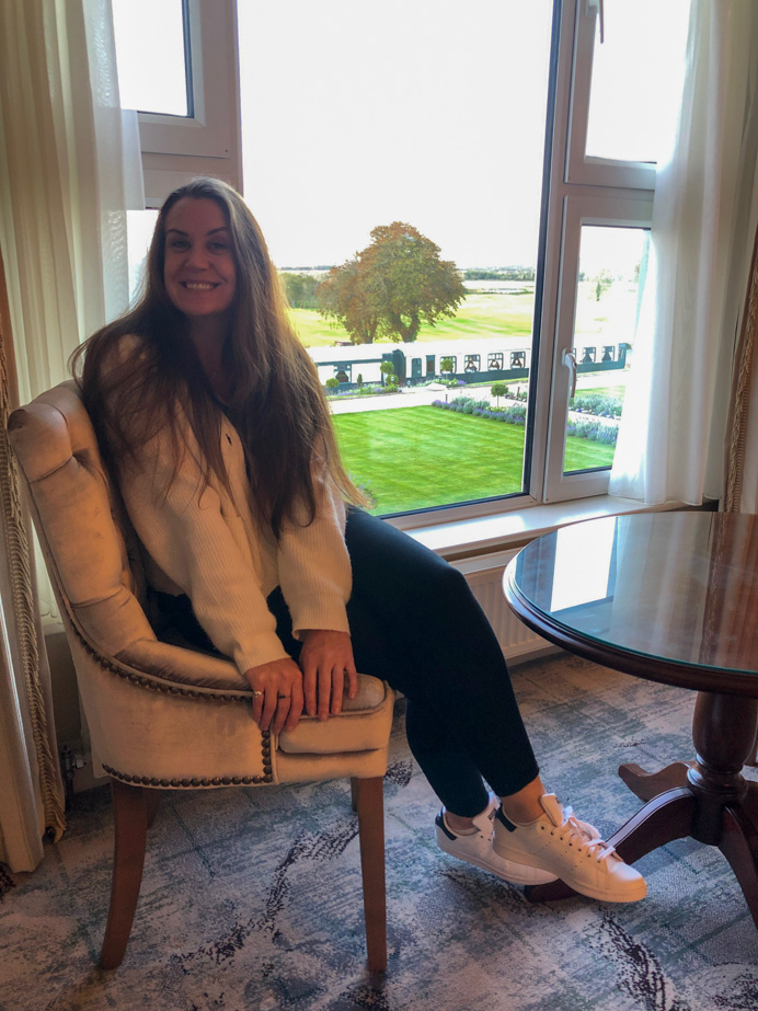 Melanie May sitting in a chair in the Glenlo Abbey Hotel and Estate Grand Suite